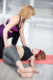 Trainer helping student to do Revolved Abdomen Pose Stock Photo