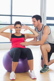 Trainer helping woman do abdominal crunches  on fitness ball. Male trainer helping young women do abdominal crunches  on fitness ball at a bright gym Royalty Free Stock Image