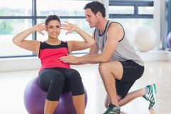 Trainer helping woman do abdominal crunches  on fitness ball. Male trainer helping young women do abdominal crunches  on fitness ball at a bright gym Stock Photo
