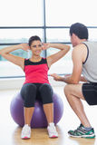 Trainer helping woman do abdominal crunches  on fitness ball. Male trainer helping young women do abdominal crunches  on fitness ball at a bright gym Stock Photos