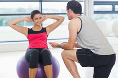 Trainer helping woman do abdominal crunches  on fitness ball. Male trainer helping young women do abdominal crunches  on fitness ball at a bright gym Stock Image