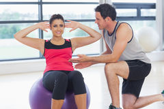 Trainer helping woman do abdominal crunches  on fitness ball. Male trainer helping young women do abdominal crunches  on fitness ball at a bright gym Royalty Free Stock Photo