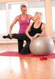 Trainer helping woman in doing exercise on ball Stock Images