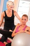 Trainer helping woman in doing exercise on ball Royalty Free Stock Photos