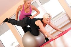 Trainer helping woman in doing exercise on ball Royalty Free Stock Photo