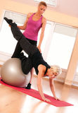 Trainer helping woman in doing exercise on ball Stock Photography