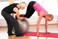 Trainer helping woman in doing exercise on ball Stock Photo