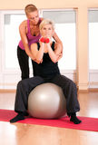 Trainer helping woman in doing exercise on ball royalty free stock images
