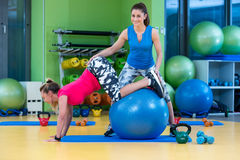 Trainer helping woman in doing exercise on ball Stock Photos