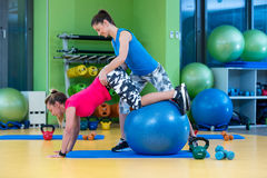 Trainer helping woman in doing exercise on ball Stock Image