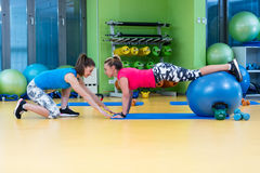 Trainer helping woman in doing exercise on ball Royalty Free Stock Image