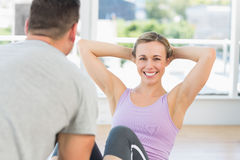 Trainer helping woman doing sit ups. Male trainer helping women doing sit ups in fitness club Stock Photos