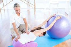 Trainer helping woman with exercise ball Stock Images