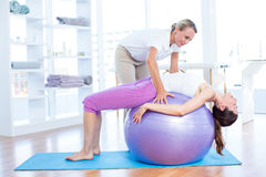 Trainer helping woman on exercise ball Stock Image