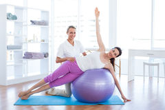 Trainer helping woman on exercise ball Royalty Free Stock Photos