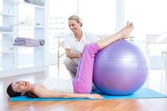 Trainer helping woman with exercise ball Stock Photos