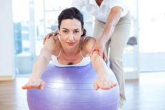 Trainer helping woman on exercise ball Royalty Free Stock Images