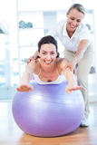 Trainer helping woman on exercise ball Stock Images