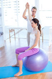 Trainer helping woman on exercise ball Royalty Free Stock Photography