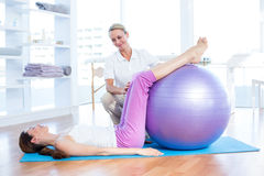 Trainer helping woman with exercise ball Stock Photo