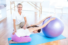 Trainer helping woman with exercise ball Royalty Free Stock Photos