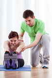 Trainer helping woman in exercises Stock Photos
