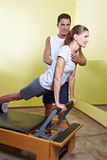 Trainer helping woman in fitness Royalty Free Stock Images
