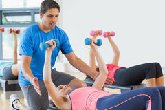 Trainer helping woman at fitness studio Royalty Free Stock Photo