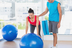 Trainer helping woman with her exercises at gym. Male trainer helping women with her exercises at a bright gym Stock Image