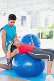 Trainer helping woman with her exercises at gym Stock Image