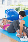 Trainer helping woman with her exercises at gym. Male trainer helping women with her exercises at a bright gym Stock Images