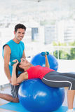 Trainer helping woman with her exercises at gym. Male trainer helping women with her exercises at a bright gym Royalty Free Stock Image