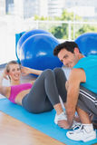 Trainer helping woman with her exercises at gym. Male trainer helping women with her exercises at a bright gym Stock Photo