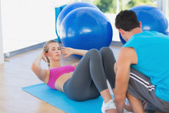 Trainer helping woman with her exercises at gym. Male trainer helping women with her exercises at a bright gym Royalty Free Stock Images