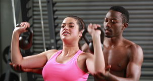 Trainer helping woman with kettlebells. At the gym stock video