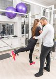 Trainer helping woman with legs training at gym. Male trainer helping young women with legs training at gym Royalty Free Stock Photos