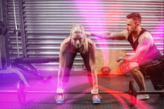 Trainer helping woman with lifting barbell. At crossfit gym Royalty Free Stock Photo