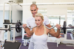 Trainer helping woman with lifting barbell in gym. Personal male trainer helping young women with lifting barbell in the gym Royalty Free Stock Photos