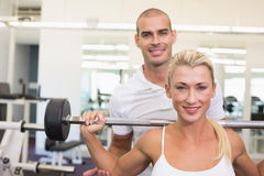 Trainer helping woman with lifting barbell in gym. Personal male trainer helping young women with lifting barbell in the gym Stock Photo