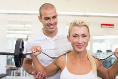 Trainer helping woman with lifting barbell in gym. Personal male trainer helping young women with lifting barbell in the gym Royalty Free Stock Image