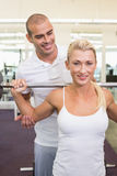 Trainer helping woman with lifting barbell in gym. Personal male trainer helping young women with lifting barbell in the gym Stock Image