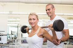 Trainer helping woman with lifting barbell in gym. Personal male trainer helping young women with lifting barbell in the gym Royalty Free Stock Photo