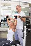 Trainer helping woman with lifting barbell in gym. Personal male trainer helping young women with lifting barbell in the gym Royalty Free Stock Photography