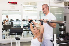 Trainer helping woman with lifting barbell in gym. Personal male trainer helping young women with lifting barbell in the gym Stock Images