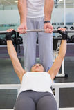 Trainer helping woman with lifting barbell in gym. Personal male trainer helping young women with lifting barbell in the gym Royalty Free Stock Images