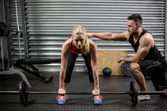 Trainer helping woman with lifting barbell Stock Images