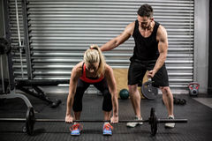 Trainer helping woman with lifting barbell Royalty Free Stock Photo