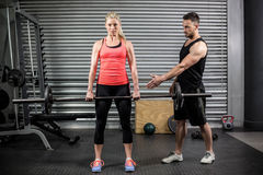 Trainer helping woman with lifting barbell Royalty Free Stock Image