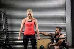 Trainer helping woman with lifting barbell Royalty Free Stock Photography