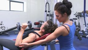 Trainer helping woman lifting weights. In gym stock video